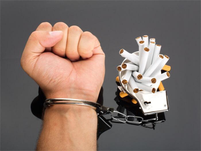 Hand an Zigaretten gekettet mit Handschelle